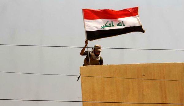 اهتزاز پرچم عراق در یکی از مناطق اطراف موصل
