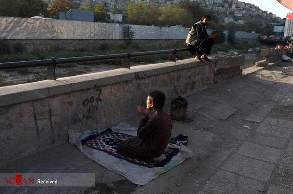 نماز کودک افغانی در هیاهوی کابل + عکس